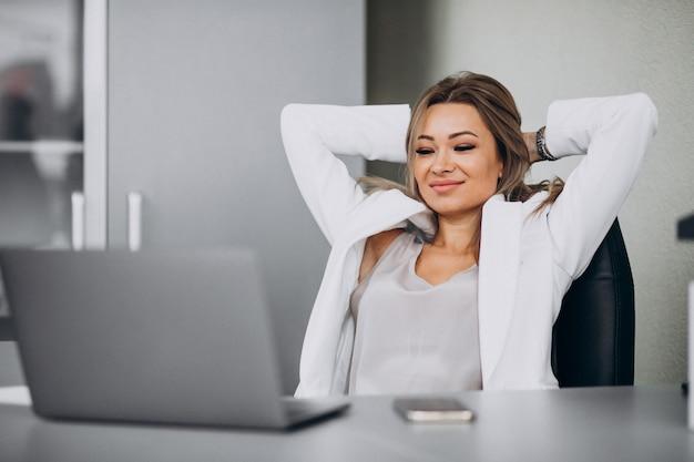 Mujer de negocios joven que trabaja en la computadora portátil en una oficina