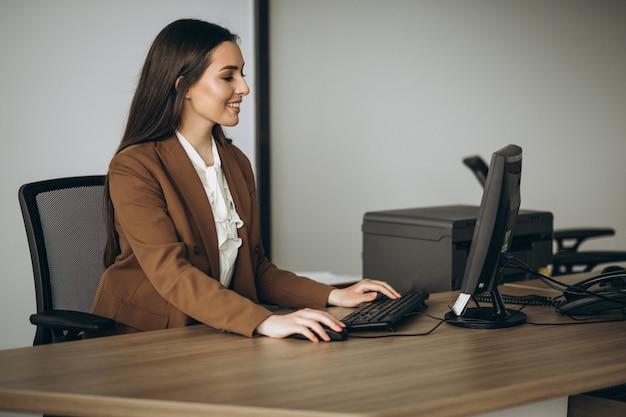 Mujer de negocios joven que trabaja en la computadora portátil en la oficina