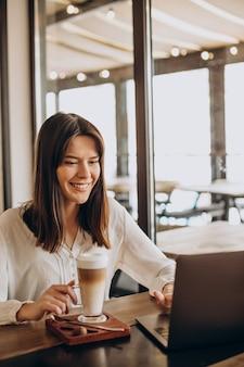 Mujer de negocios joven que trabaja en línea en un café y tomando café
