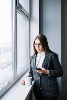 Mujer de negocios joven que usa smartphone en la ventana