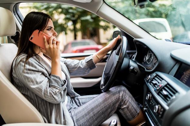 Mujer de negocios joven que usa su teléfono mientras conduce el coche