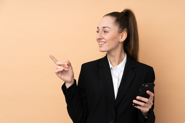Mujer de negocios joven que usa el teléfono móvil sobre la pared aislada que señala al lado para presentar un producto