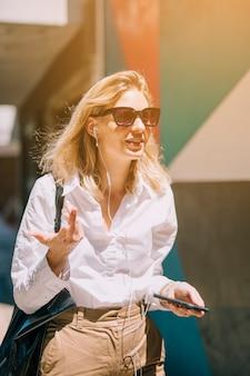Mujer de negocios joven rubia en música que escucha de la luz del sol en gesticular del teléfono móvil Foto gratis