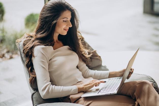 Mujer de negocios joven sentada en un cahir y trabajando en equipo