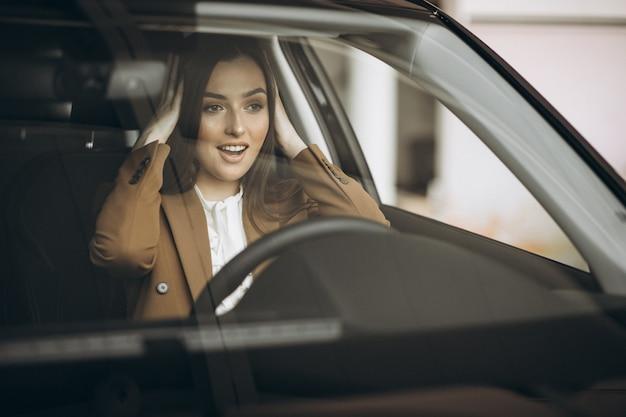 Mujer de negocios joven sentada en el coche