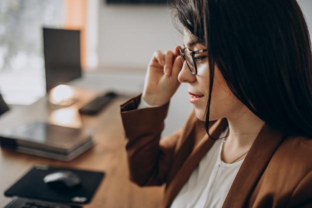 Mujer de negocios joven sentado en el escritorio y trabajando en equipo