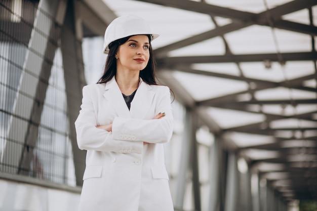 Mujer de negocios joven con sombrero duro en el objeto de construcción