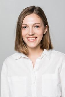 Mujer de negocios joven sonriente contra la pared blanca.