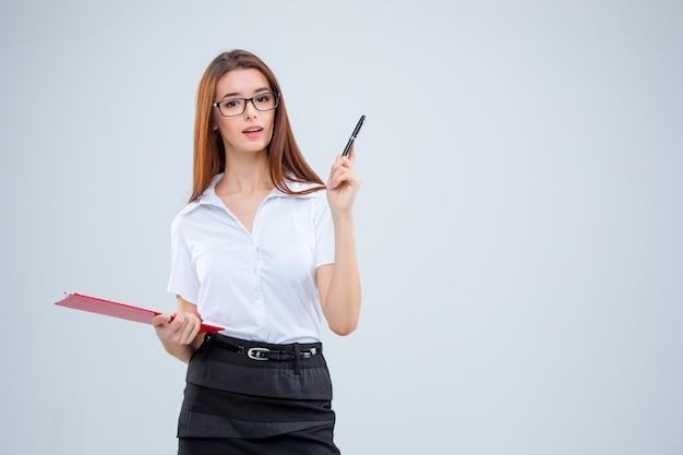 La mujer de negocios joven sonriente con lápiz y tableta para notas en gris