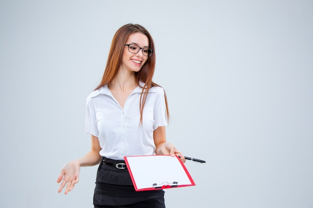 La mujer de negocios joven sonriente con lápiz y tableta para notas en la pared gris