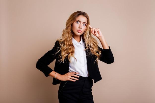 Mujer de negocios joven sorprendida o empleado en elegante traje posando sobre pared beige.
