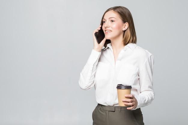 Mujer de negocios joven sosteniendo una taza de café y un teléfono sobre blanco aislado