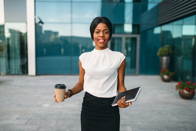 Mujer de negocios joven con taza de café de cartón y bloc de notas contra el edificio de oficinas