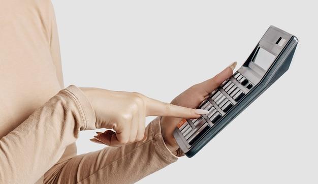 Mujer de negocios joven tiene calculadora aislada sobre fondo gris. lograr el concepto de contabilidad empresarial de riqueza profesional.