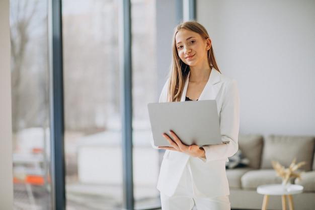 Mujer de negocios joven en traje blanco trabajando en una computadora