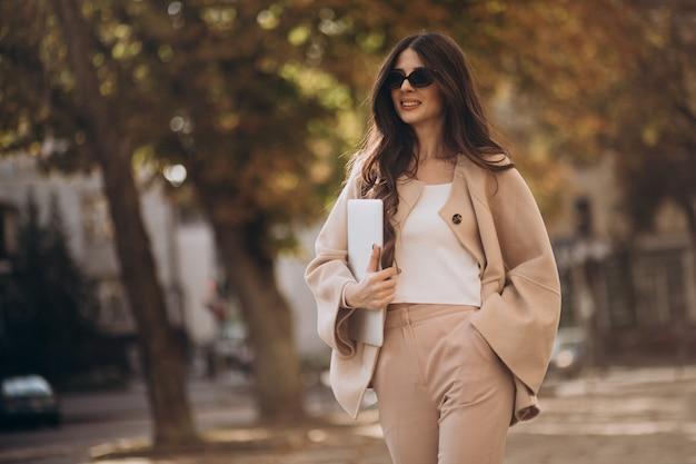 Mujer de negocios joven en traje de negocios con portátil en la calle