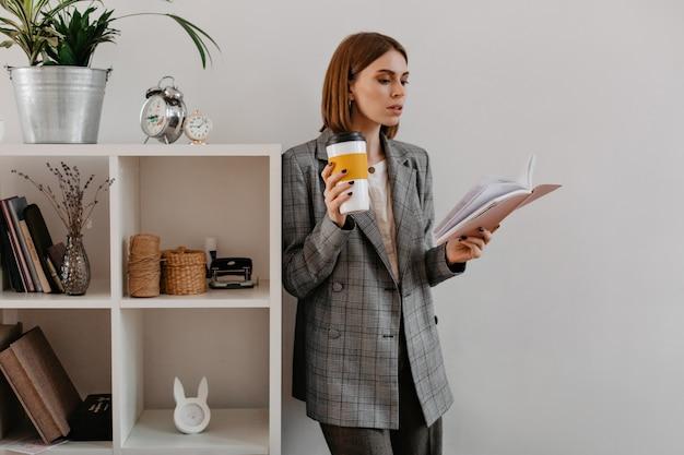 Mujer de negocios joven con un vaso de café en sus manos, fascinada por la lectura, se encuentra apoyada en el estante con accesorios de trabajo.