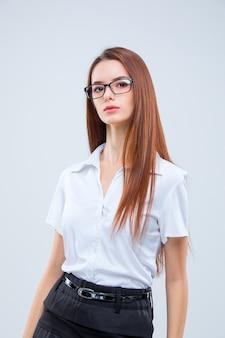 Mujer de negocios joven en vasos sobre un fondo gris