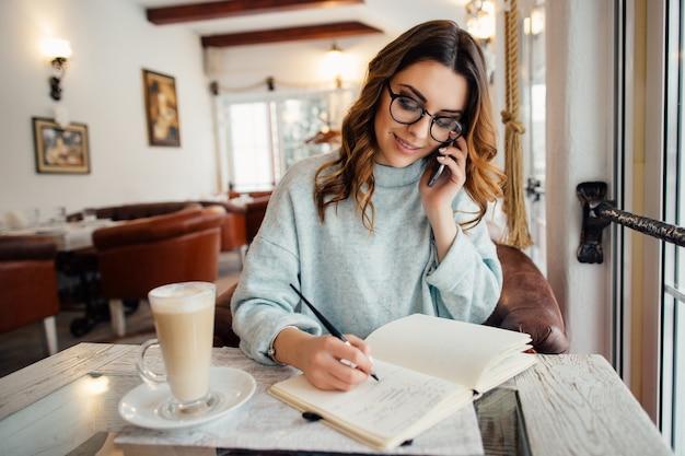 Mujer de negocios joven en vidrios que conduce la conversación de negocios en el teléfono