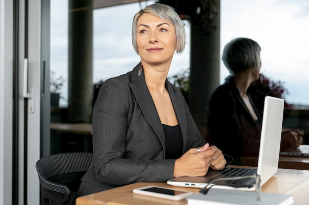 Mujer de negocios con laptop mirando a otro lado