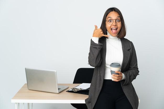 Mujer de negocios latina joven que trabaja en una oficina aislada sobre fondo blanco haciendo gesto de teléfono. llámame señal
