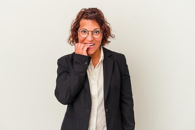 Mujer de negocios latina de mediana edad aislada sobre fondo blanco mordiéndose las uñas, nerviosa y muy ansiosa.