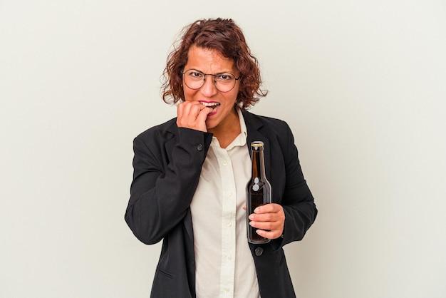 Mujer de negocios latina de mediana edad sosteniendo una cerveza aislada sobre fondo blanco mordiéndose las uñas, nerviosa y muy ansiosa.