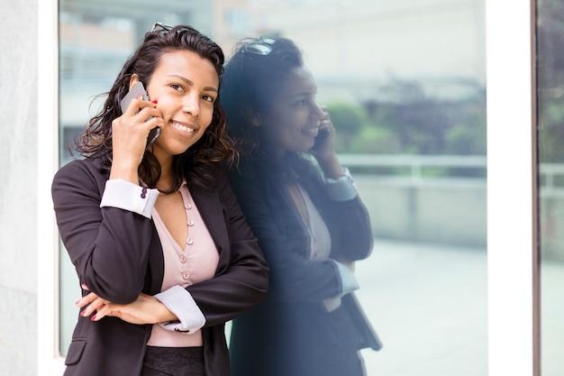 Mujer de negocios latinoamericana joven hablando por teléfono en su lugar de trabajo. espacio para texto.