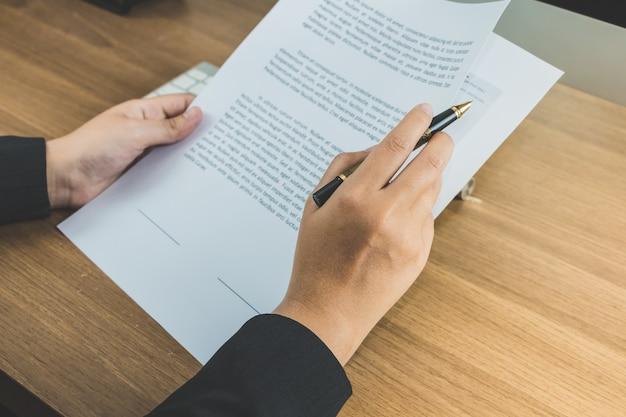 Mujer de negocios, lectura, términos, y, condición, papel, en, tabla, firma, concepto