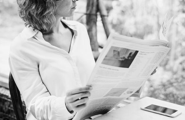 Mujer de negocios leyendo periódico en la mañana