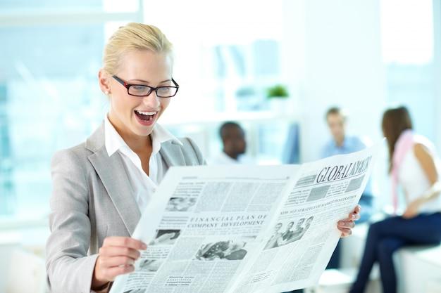 Mujer de negocios leyendo un periódico
