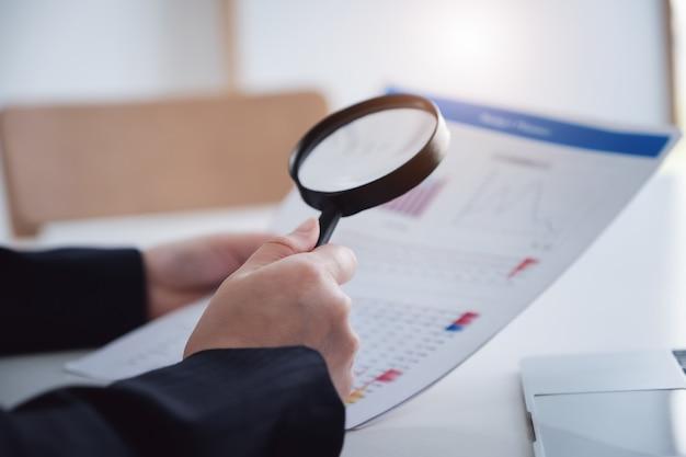 Mujer de negocios con lupa para revisar el balance anual. auditar y verificar integridad antes del concepto de inversión.