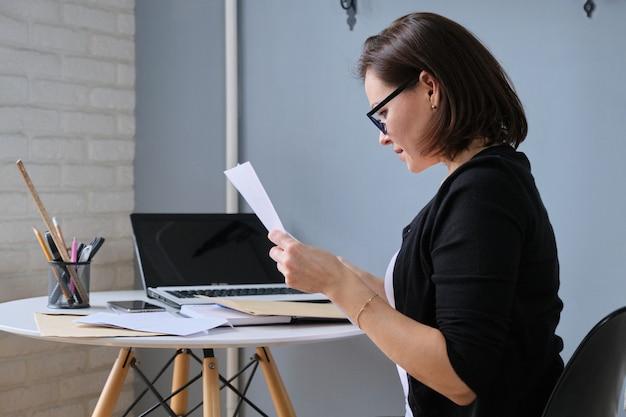 Mujer de negocios madura sentada en un escritorio en la oficina leyendo un documento en papel