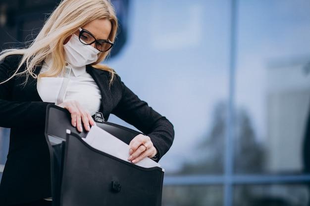 Mujer de negocios con máscara fuera del centro de negocios