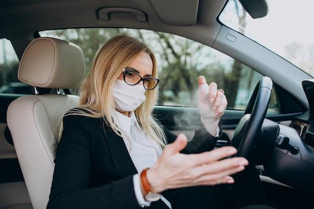 Mujer de negocios en máscara de protección sentado dentro de un automóvil con antiséptico