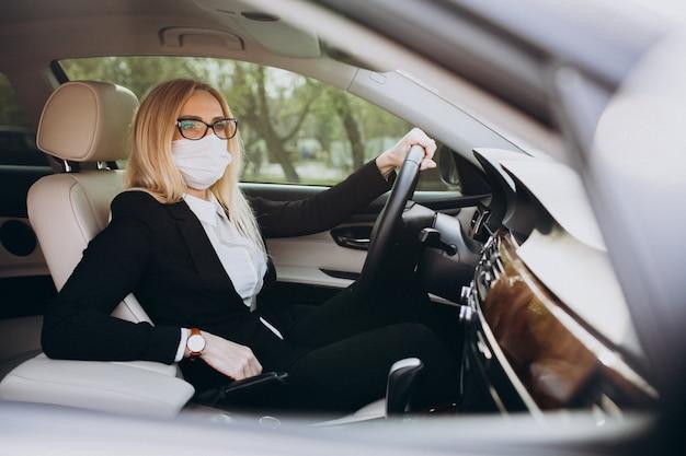 Mujer de negocios con máscara de protección sentado dentro de un automóvil