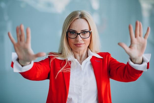 Mujer de negocios mayores mostrando las manos en la chaqueta roja