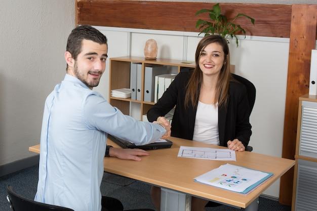Mujer de negocios mientras estrecha la mano en el escritorio de oficina