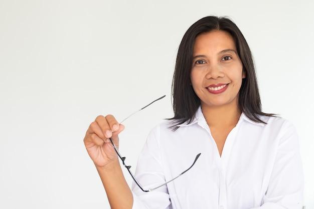 Mujer de negocios moderna en la camisa blanca que sostiene los vidrios disponibles en el fondo blanco