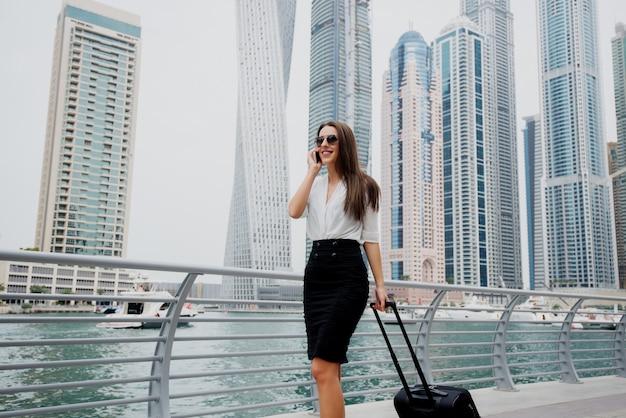 Mujer de negocios moderna joven ocupada en traje tirando de una maleta en un marine de dubai. caminando hacia su oficina y hablando por teléfono.