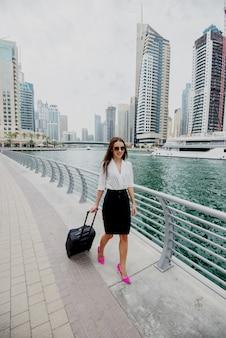 Mujer de negocios moderna joven ocupada en traje tirando de una maleta en un marine de dubai. caminando hacia su oficina.