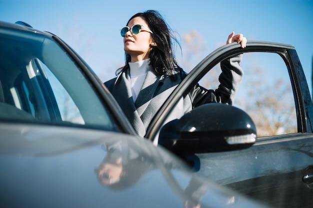Mujer de negocios moderna de pies al lado de coche