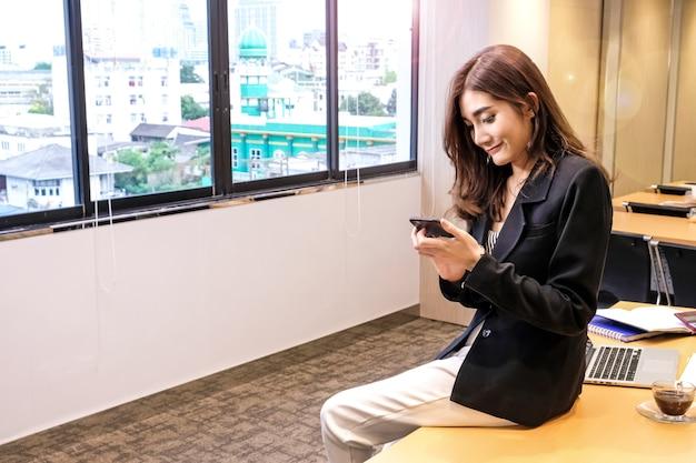 Mujer de negocios moderno con smartphone en su lugar de trabajo en la oficina