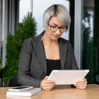 Mujer de negocios montando tableta fron maqueta