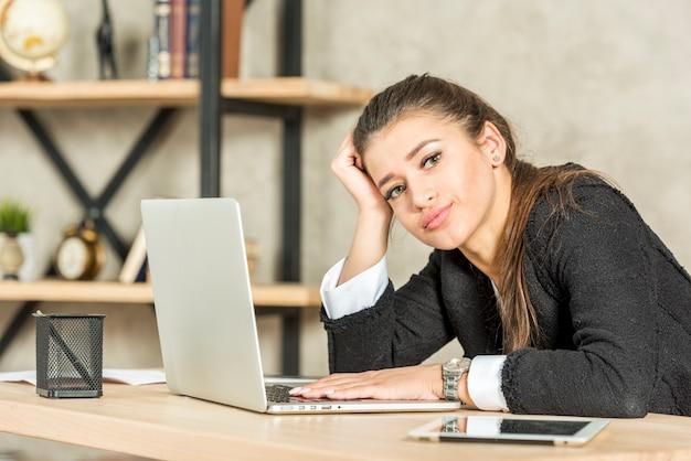 Mujer de negocios morena aburrida en su oficina