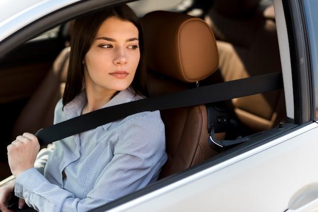 Mujer de negocios morena dentro de un coche