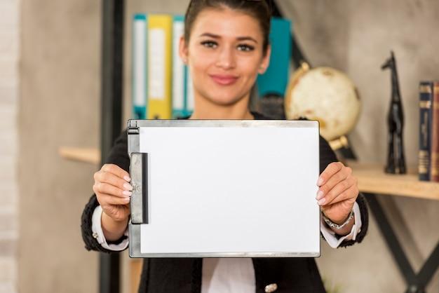 Mujer de negocios morena enseñando papel