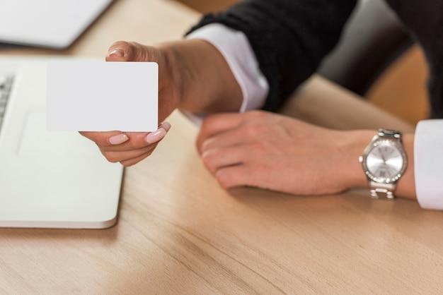 Mujer de negocios morena  enseñando tarjeta vacía