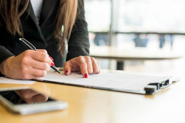 Mujer de negocios morena escribiendo en un documento