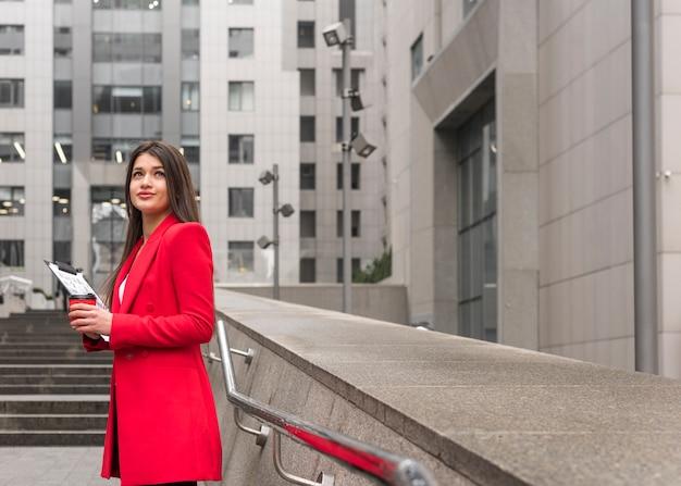 Mujer de negocios morena en exterior con abrigo rojo